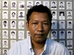 Bo Kyi of the Assistance Association for Political Prisoners Museum sits in front of photographs of hundreds of Myanmar political prisoners, in Mae Sot, Thailand, on Tuesday, Oct. 2, 2007.   Many feel the beatings and torture they endued in Myanmar's prisons in past years is happening again following the most recent crackdown. (AP Photo/David Longstreath)